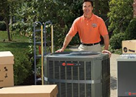 A Houston air conditioning installation technician standing behind an outdoor unit