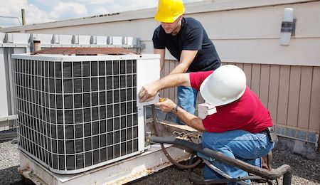 Two HVAC technicians repairing  an air conditioning unit on the roof of a building in Houston.