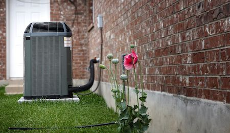 An outdoor AC unit connected to a brick wall and resting on a lush green lawn